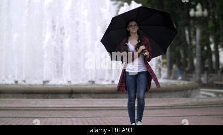 girl with an umbrella in the park on a background of a fountain - Stock Photo