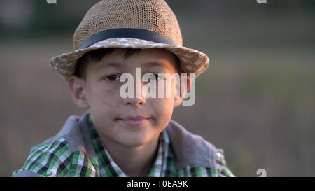 portrait of a village boy in a straw hat looking into the camera at sunset - Stock Photo