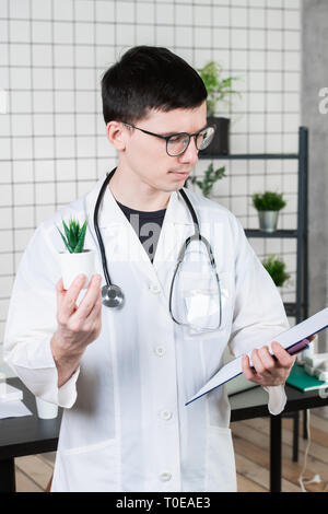 Scientist Conducts Experiments with a green Plant - Stock Photo