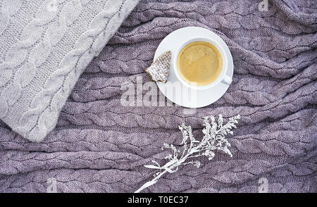 White cup coffee with cookie in form fir and nice white flower on pillow and warm woolen gray pink plaid. Knitted textile with braid pattern. Winter autumn concept of comfort and relaxation. - Stock Photo