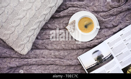 White cup coffee with cookie in form fir and white phone flower on gray pillow and warm woolen gray pink plaid. Knitted textile with braid pattern. Winter autumn concept of comfort - Stock Photo