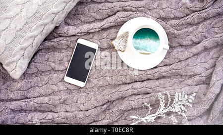 White cup coffee with turquoise sea waves and waffle cookie in form fir and white phone flower on pillow and warm woolen gray plaid. Knitted textile with braid pattern. Winter autumn concept comfort - Stock Photo
