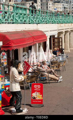 Holidaymakers enjoying refreshments sitting outside a cafe on the seafront in Brighton, Sussex, England. - Stock Photo