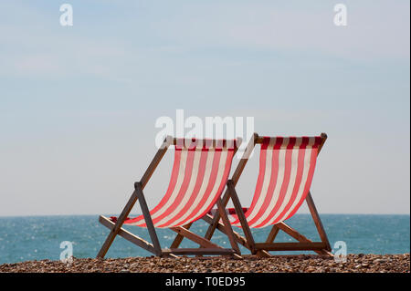Pair of traditional wooden deckchairs on the beach in Brighton, Sussex, England. - Stock Photo