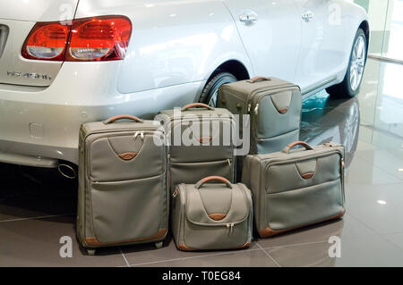 A selection of luggage near a car boot on display in a Lexus car showroom - Stock Photo