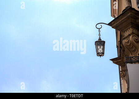 Old metal lantern hanging on building by blue sky background. Vintage lamp on house wall with copy space - Stock Photo