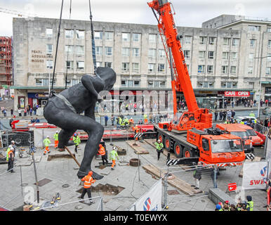 The largest cast bronze sculpture in the UK, The Messenger, being lowered into position outside the Theatre Royal Plymouth. - Stock Photo