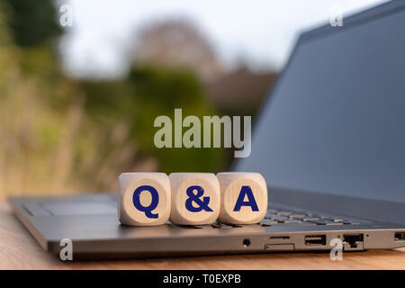 Symbol for Questions and Answers. Cubes placed on a notebook with the letters 'Q & A'. - Stock Photo