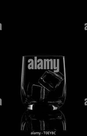 Empty glass filled with ice cubes o na black black and white - Stock Photo