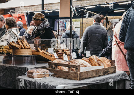London, UK - March 16. 2019: People buying fresh bread and pastries from a market stall at Greenwich Market, London's only market set within a World H - Stock Photo