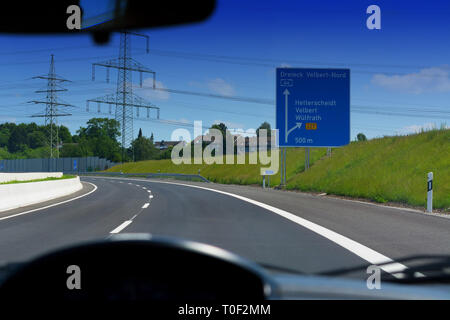 German motorway sign with inscription in German Driving direction to the cities - Velbert, Heiligenhaus, Wuelfrath and Hetterscheidt - Stock Photo