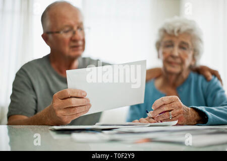 Anxious elderly couple are worried about a bill that they have received. - Stock Photo