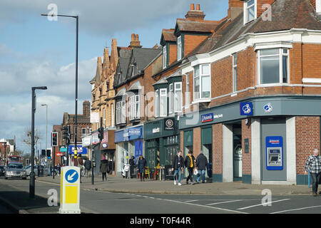 A busy high street with shoppers and traffic in the UK - Stock Photo