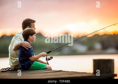Father and son fishing from a pier. - Stock Photo