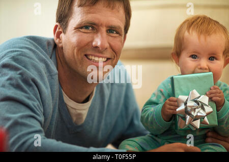 Happy father opening presents with his baby daughter. - Stock Photo