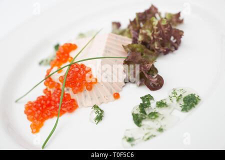 Cheese dish topped with red caviar on porcelain plate - Stock Photo