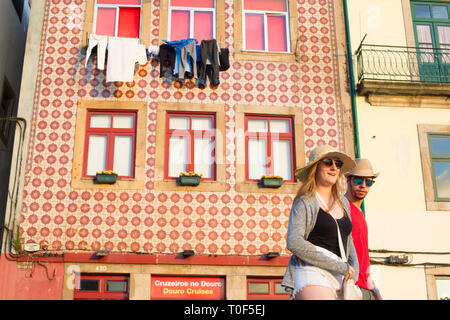 PORTO, PORTUGAL - JUNE 2, 2017: Couple of tourists in sunglasses walking by old town street of Porto, traditional house wall decorated with red tiles, - Stock Photo