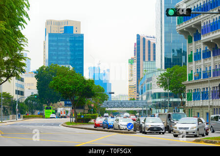 SINGAPORE - JANUARY 14, 2017: Metropolis cityscape, cars and green traffic light on downtown street road - Stock Photo