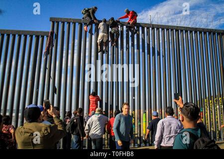 Baja California, Mexico. 19th Mar, 2019. Dozens of migrants try to enter the United States illegally from the Playas Tijuana area in the Mexican state of Baja California, Mexico, 19 March 2019. Around 16.00 local time (23.00 GMT), the migrants, almost a hundred according to the witnesses, arrived at the seashore in the Mexican town to try to jump the metal fence that in this area delimits the border between the two countries. EFE/Joebeth Terriquez Credit: EFE News Agency/Alamy Live News - Stock Photo