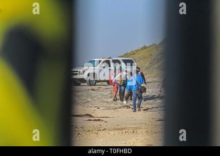 Baja California, Mexico. 19th Mar, 2019. Dozens of migrants walk through US territory after jumping the metal fence located in the Playas Tijuana area in the Mexican state of Baja California, Mexico, 19 March 2019. Around 16.00 local time (23.00 GMT), the migrants, almost a hundred according to the witnesses, arrived at the seashore in the Mexican town to try to jump the metal fence that in this area delimits the border between the two countries. Without any Mexican authority to prevent them, one by one the migrants managed to cross into US territory and at least it was observed that a score o - Stock Photo