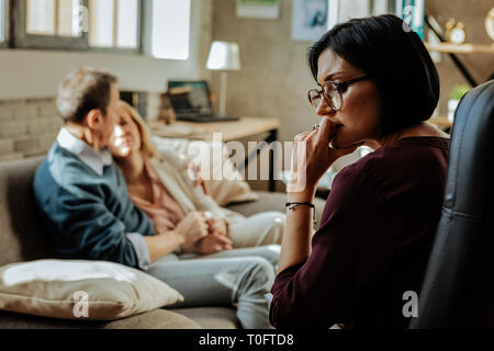 Puzzled doctor with bob haircut thinking about situation in family - Stock Photo