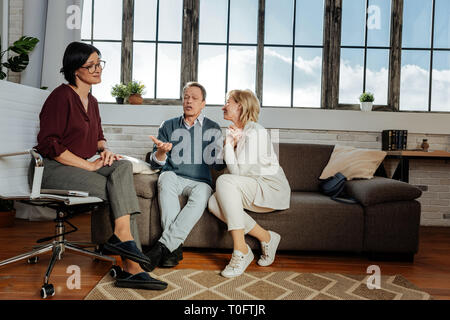 Expressive good-looking couple sitting next to each other and talking about themselves - Stock Photo