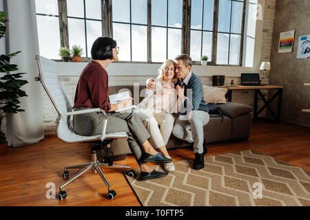 Desperate good-looking couple sitting closely to each other - Stock Photo