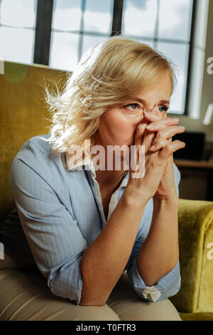 Serious blonde woman wearing tidy blue shirt and deeply thinking - Stock Photo