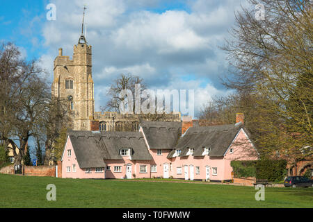 Thatched cottage painted in Suffolk pink with St. Mary the Virgin's Church on the village green. Cavendish, Suffolk, East Anglia, UK. - Stock Photo