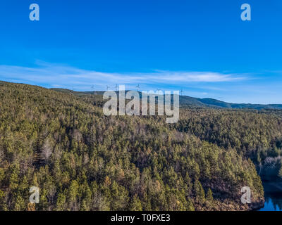 Aerial view of drone, forest in mountain with wind turbines on ridge, in Portugal - Stock Photo