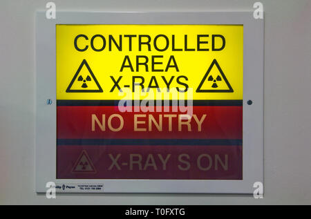 Illuminated x-ray sign showing x-rays are in progress, warning people not to enter the room. - Stock Photo