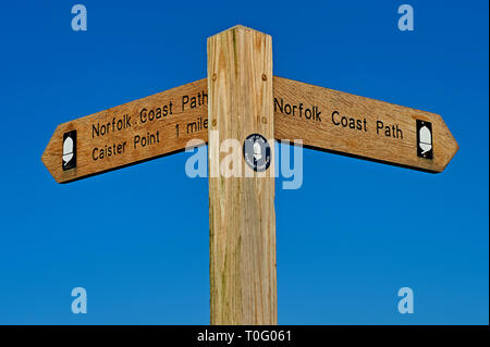 Wooden finger post sign against a blue sky - Stock Photo