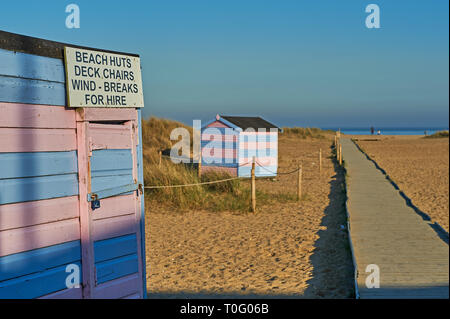 Traditional seaside beach huts in blue and pink stripes on the shingle coastal strip in Great Yarmouth, Norfolk - Stock Photo