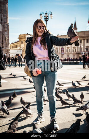 Pigeon flying near people in central square, Milan, Italy - Stock Photo