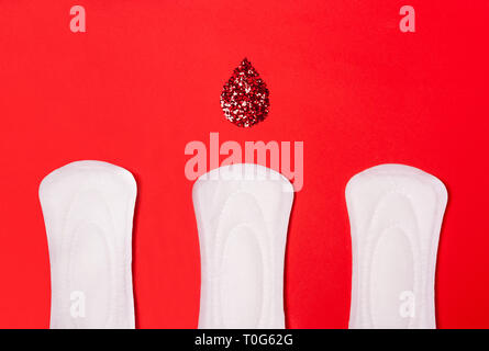 Three sanitary pads on a coral red background. The concept of critical days, menstruation, women's periodic cycle. - Stock Photo
