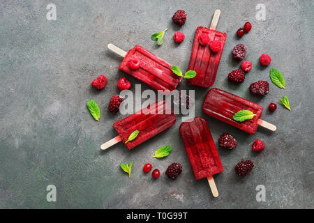 Flat lay homemade raspberries blackberry ice cream popsicles decorated berries and mint leaves on gray background.A refreshing summer dessert,top view - Stock Photo