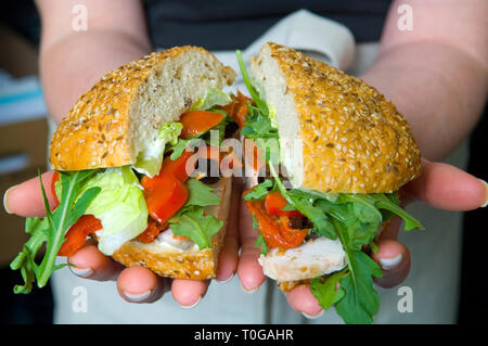 A delicious sandwich, roll, with lots of fresh ingredients, fillings. - Stock Photo