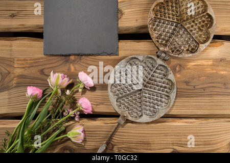 Traditional ancient waffle iron arranged on rustic wood planks with slate board and bunch of flowers. Shot from above, flat lay. - Stock Photo