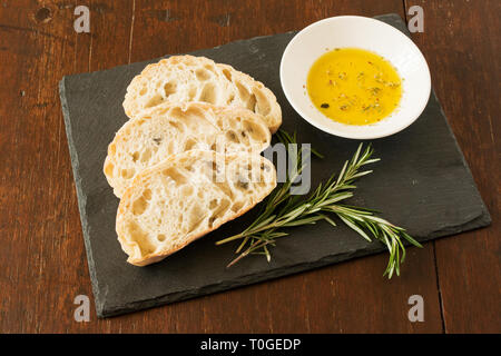 Three slices of ciabatta bread on a slate board with springs of rosemary and a bowl of herb-infused extra virgin olive oil on a distressed wood table. - Stock Photo