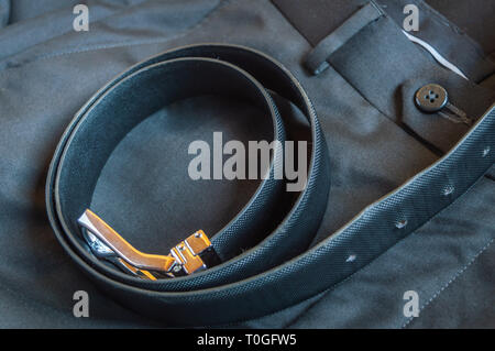 A black leather belt kept on a formal pant trouser - Stock Photo