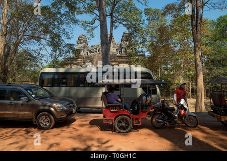 Tourists and vehicles  line up in front of the Khmer temple, Ta Keo, at Angkor in Siem Reap, Cambodia. - Stock Photo