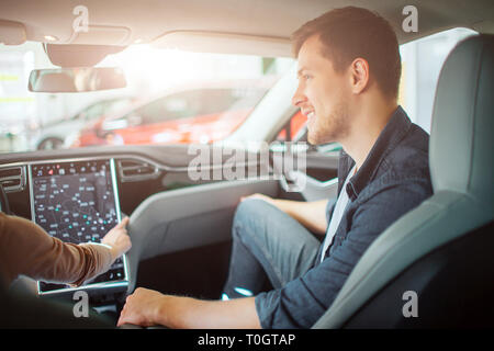 Young couple buying first electric car in the showroom. Attractive glad man looking at his girlfriend while she chooising a way on electronic - Stock Photo