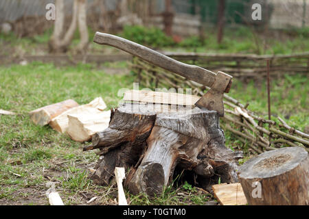 Old axe in tree stump on cottage glade at summer day - Stock Photo
