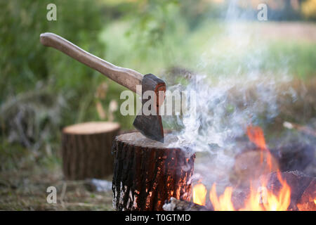Axe in tree stump and campfire with smoke in summer forest at evening - Stock Photo