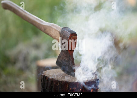 Axe in tree stump and smoke from campfire - Stock Photo