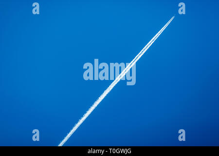 Commercial airline jet contrails across a clear blue sky - Stock Photo