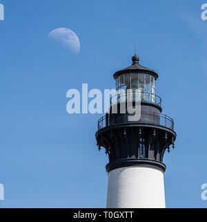 The top light of a lighthouse on the outer banks of North Carolina next to a half moon - Stock Photo