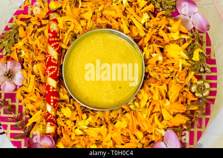 Traditional Haldi turmeric kept on a flower plate for the hindu marriage ceremony - Stock Photo