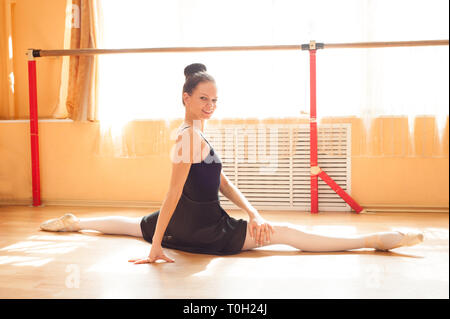 Ballerina dancer warming up in the sunny hall - Stock Photo