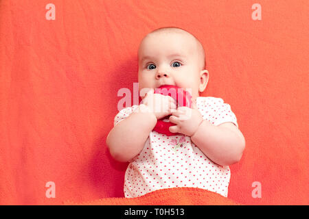 Head and shoulders portrait of little baby girl chewing teething ring laying on living coral trendy color blanket - Stock Photo